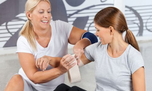 Woman bandaging an injured woman's upper arm