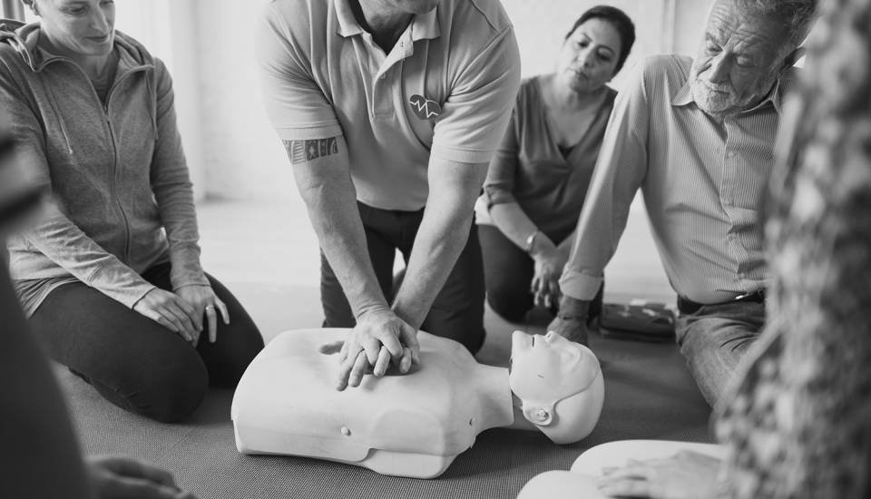CPR being demonstrated on a mannikin at a First Aid course