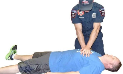 First Aid CPR chest compressions being performed on unconscious man